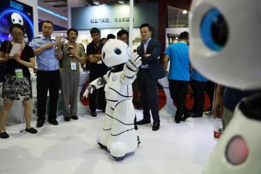 Varias personas observan un robot en la Feria Beijing International  - FOTO: EFE