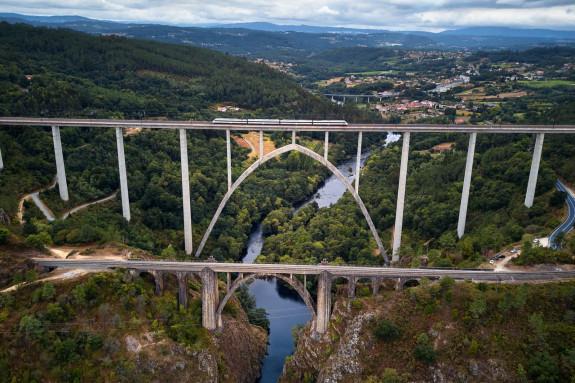 Un tren atravesando el nuevo viaducto construido en paralelo al antiguo puente de Gundián (Vedra)   - FOTO: Deensel