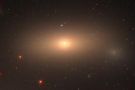 Imagen a color del telescopio espacial Hubble (HST) de la galaxia masiva reliquia NGC1277. La imagen se construyó utilizando los filtros F475W, F625W y F850LP que cubren el rango visible de la radiación. Los datos se obtuvieron con el programa HST GO-14215 (cuyo investigador principal es Ignacio Trujillo). El campo de visión que se muestra corresponde a una escala física de aproximadamente 50000 x 35000 años luz. La imagen se ha escalado con una intensidad logarítmica para facilitar ver las diferentes estructuras de la galaxia. La gran mayoría de los puntos que se observan en la imagen rodeando la galaxia son cúmulos globulares.  - FOTO: Michael Beasley e Ignacio Trujillo
