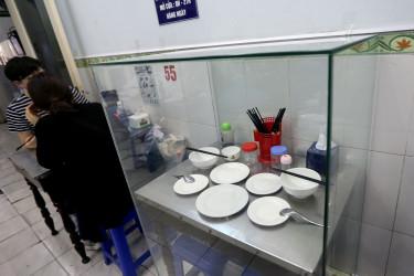 Varias personas comen junto a una mesa en la que se sentó el expresidente estadounidense Barak Obama, preservada dentro de una vitrina, en el restaurante Bun cha Huong Lien en Hanói (Vietnam) - FOTO: EFE/ Luong Thai Linh