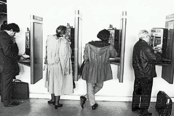 Varias personas hablando por teléfono desde las cabinas del viejo aeropuerto de Lavacolla en 1992 - FOTO: Fernando Blanco
