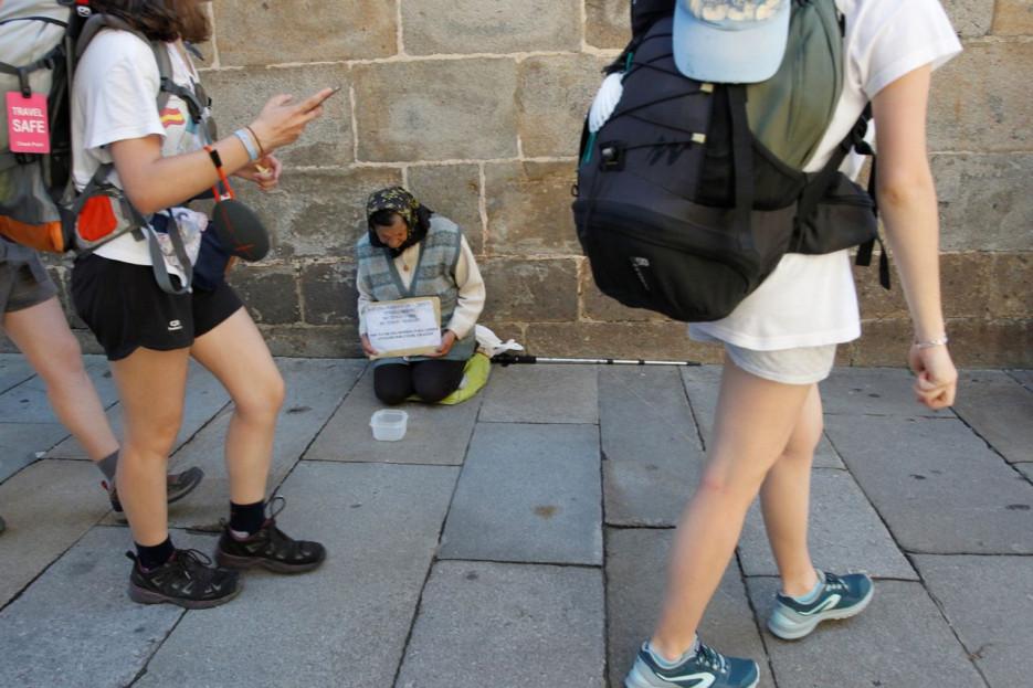 Una persona pidiendo limosna a los transeúntes en las inmediaciones de la Catedral de Santiago - FOTO: Antonio Hernández
