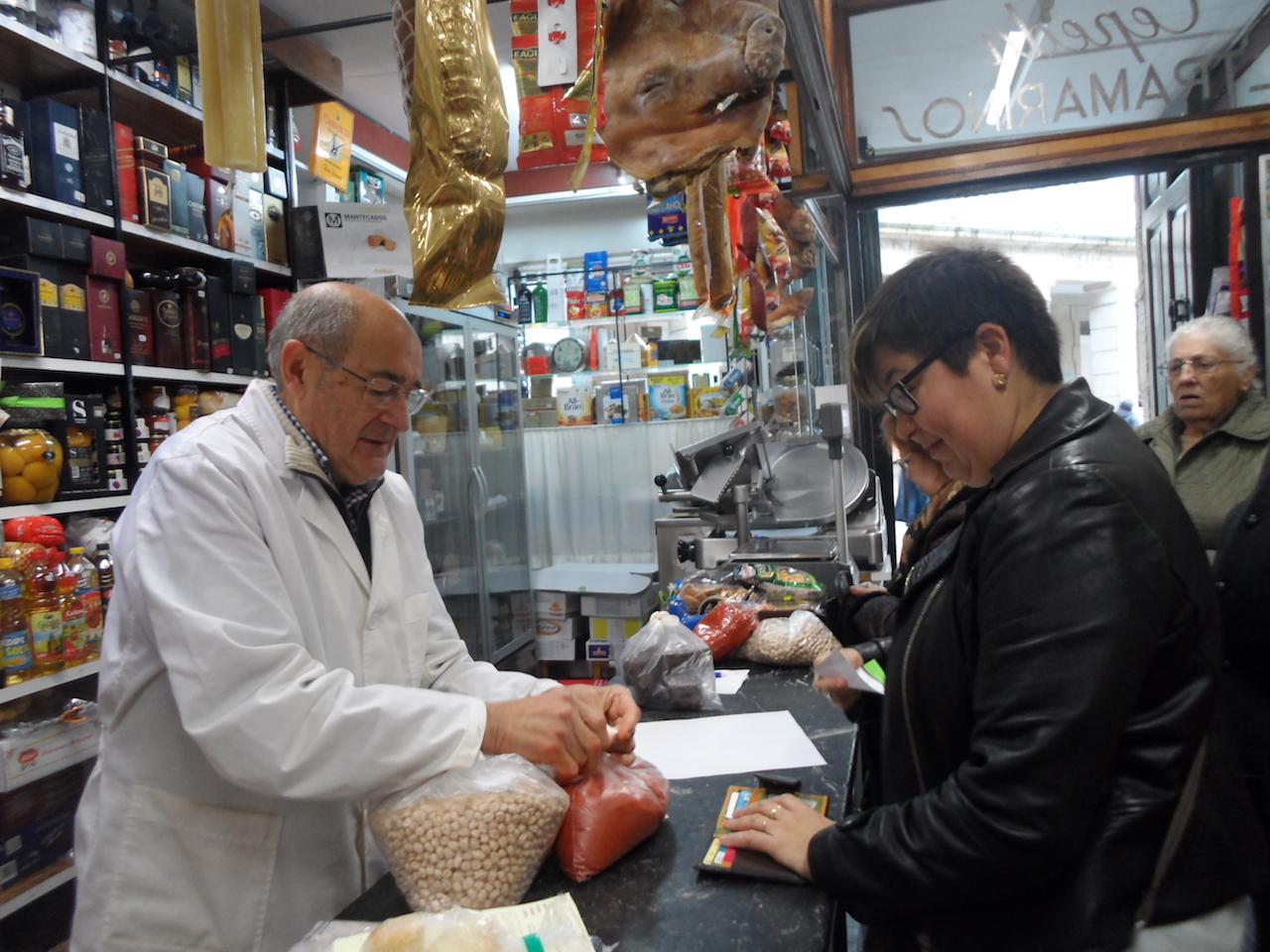José Luis Cepeda despachando a unha das súas clientas no ultramarinos da praza de Cervantes 9 - FOTO: G.L.O.