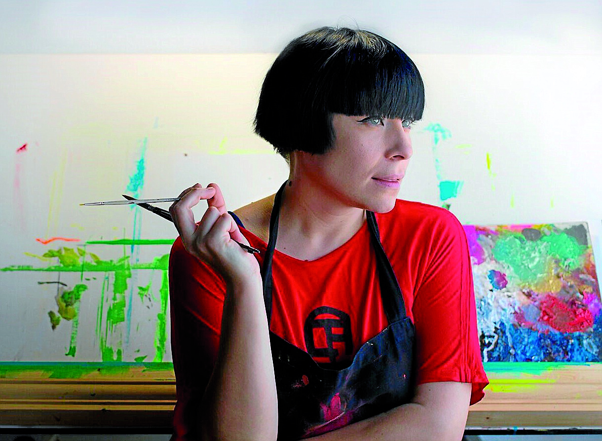 La artista moldava Natasha Lelenco posa con sus pinceles y, detrás de ella, la mesa de trabajo y la paleta - FOTO: ecg