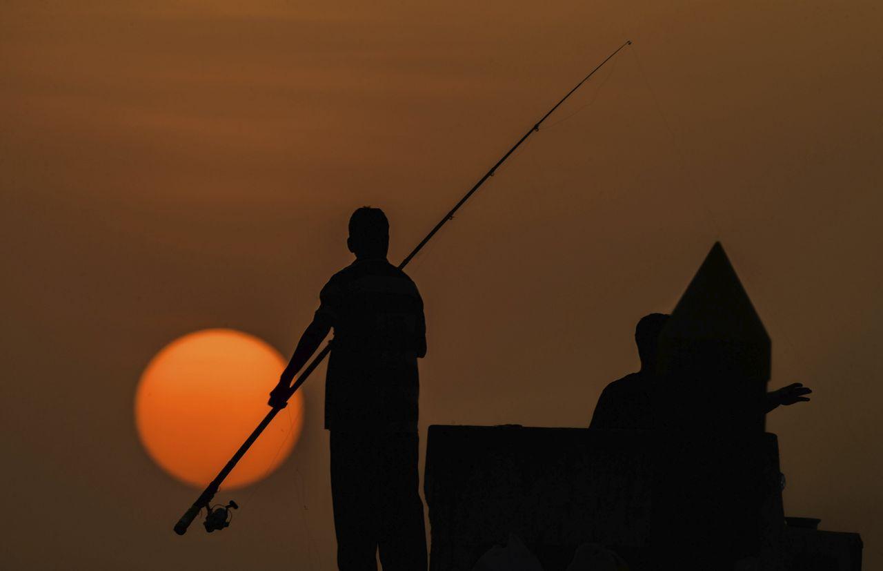 Vista de las siluetas de unos pescadores durante una puesta de sol en Kuwait, 21 de agosto de 2017 - FOTO: Efe
