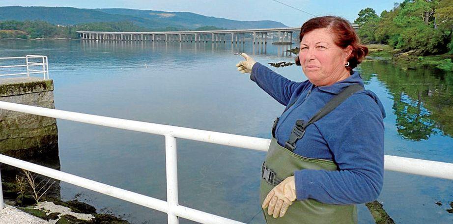 Una mariscadora señala el punto en el que se encontró el móvil de Diana bajo el viaducto de Taragoña - FOTO: Suso Souto