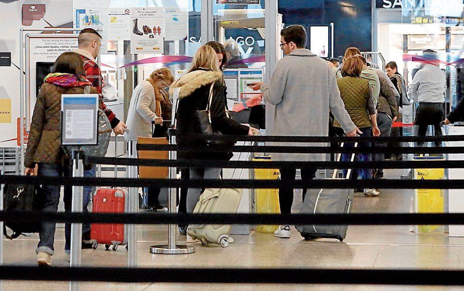 Pasajeros en la cola del control de seguridad del aeropuerto de Lavacolla, con sus maletas de mano - FOTO: ECG