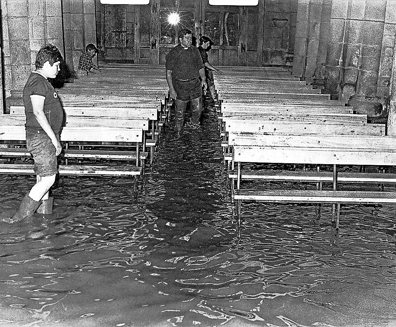El párroco de Sar, José Porto, con botas de agua, dentro de la Colegiata completamente inundada. - FOTO: ECG