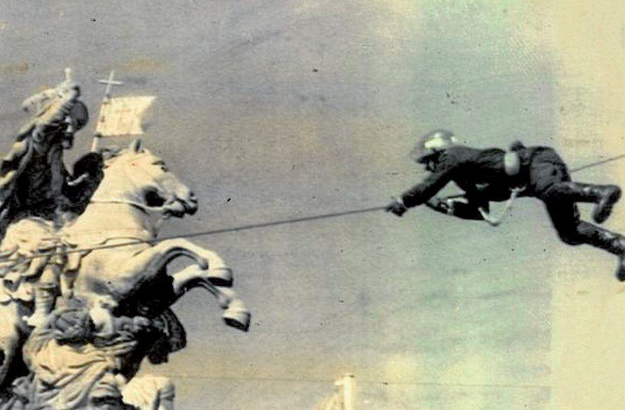 Un bombero se desplaza encaramado a un cable a 30 metros de altura en la plaza del Obradoiro - FOTO: A. Suárez/Efe