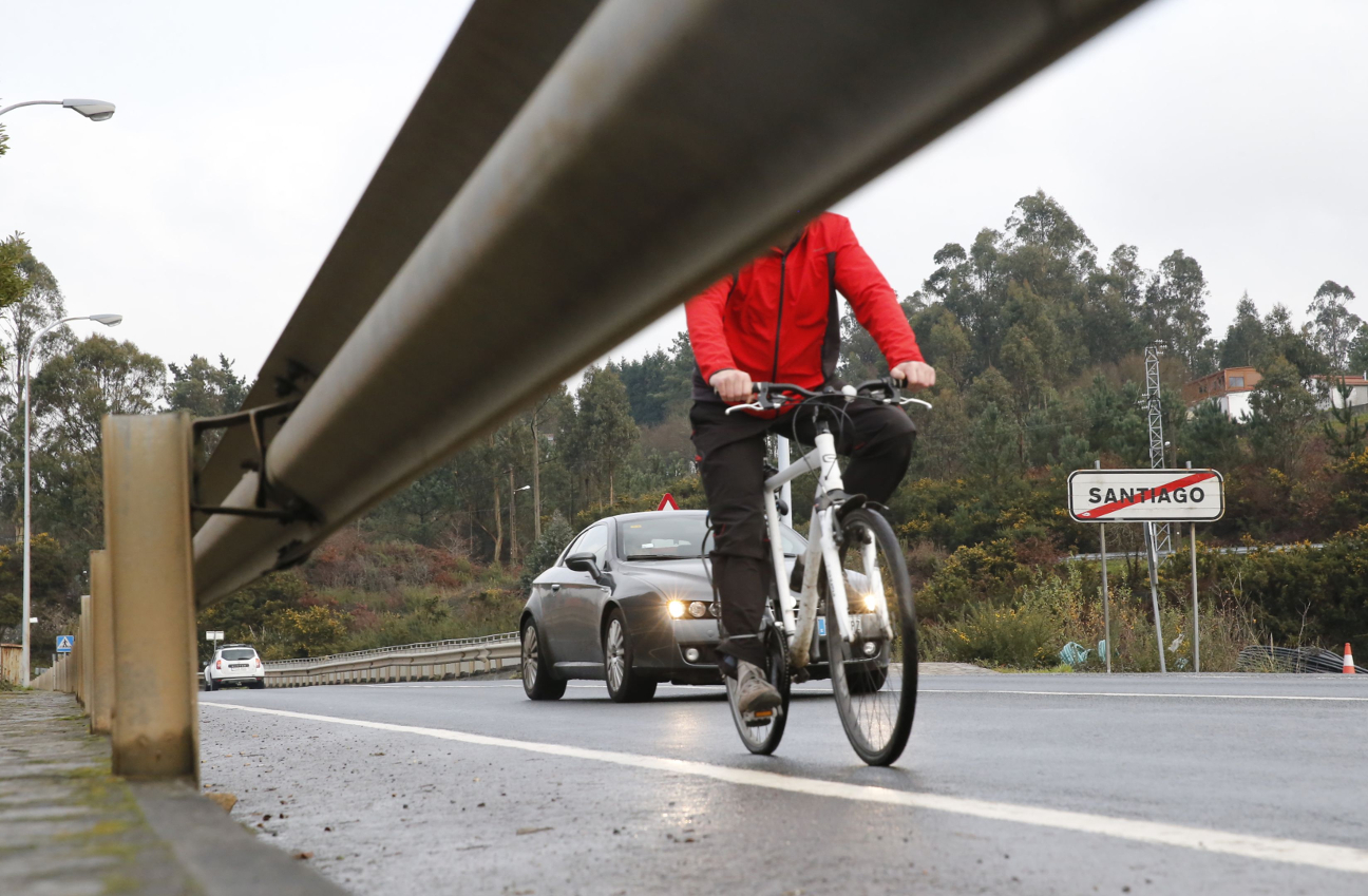 Un vehículo circulando detrás de un ciclista por una carretera de la capital gallega, en una imagen de archivo.  - FOTO: ECG